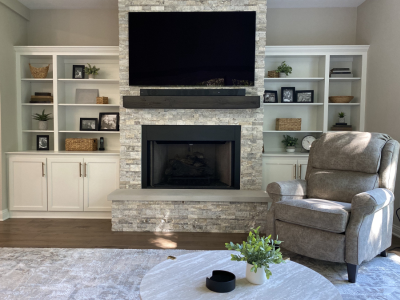 Image of a living area with a tv above a fireplace.